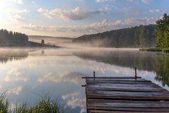 Sunrise over the foggy river with a wooden pier. Foggy summer sunrise over the river with a wooden pier stock photo