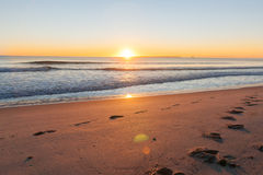 Sunrise over footprints on beach Royalty Free Stock Photo