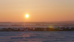 Sunrise over frozen snow-covered russian rustic landscape, telephoto. Shot stock video
