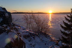 Sunrise over frozen and snowy lake Stock Photos
