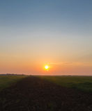 Sunrise over furrow and field. Sun rises over a wheat field, as seen from a furrow, in the early morning Royalty Free Stock Photo