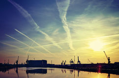 Sunrise over harbor cranes silhouettes with dramatic sky. Royalty Free Stock Photos