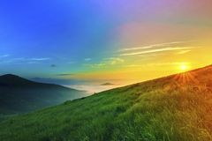 Sunrise over hills in mountains with green grass and blue sky wi. Th white clouds Royalty Free Stock Images
