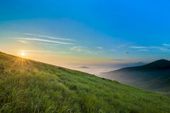 Sunrise over hills in mountains with green grass and blue sky wi Royalty Free Stock Photo