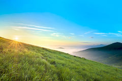 Sunrise over hills in mountains with green grass and blue sky wi Royalty Free Stock Photography