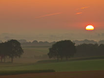 Sunrise over hilly farmland. The sunis is rising over misty hilly farmland Stock Photography