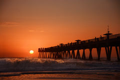 Sunrise over horizon and fishing pier. Sun rising over horizon and fishing pier, beach illuminated with sunlight. People standing on the pier. Jacksonville royalty free stock photography