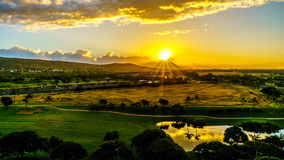 Sunrise over the horizon with sun peeking under dark morning clouds Stock Photography