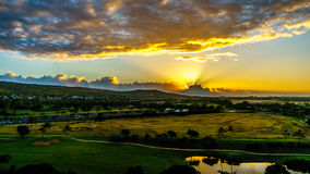 Sunrise over the horizon with sun peeking under dark morning clouds Royalty Free Stock Photos