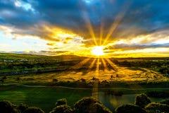 Sunrise over the horizon with sun peeking under dark morning clouds Stock Photo