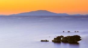 Sunrise over island in sea. Colorful orange sunset over island in sea with rocks silhouetted in foreground Stock Image