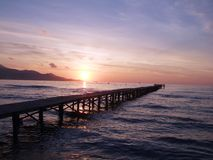 Sunrise over jetty. Sun rise, with wooden jetty in foreground royalty free stock image