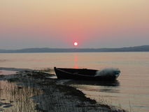 Sunrise over lagoon with small fishing boat on beach Stock Photos