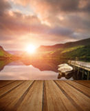 Sunrise over lake with boats moored at jetty with wooden planks Stock Photo