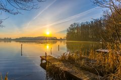 Sunrise over lake at end of winter Stock Photos