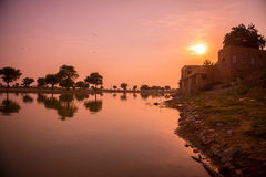 A sunrise over a lake in India Stock Image