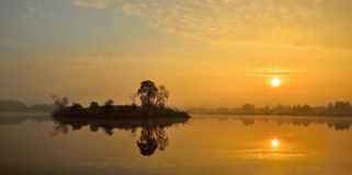 Sunrise over a lake with a lonely island. Stock Photography