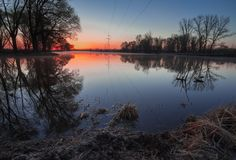 Sunrise over the lake with reflection of bare trees in the water. Stock Image