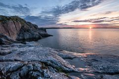 Sunrise over lake with stony coast under cloudy morning sky in y Royalty Free Stock Images