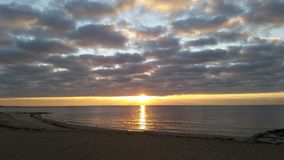Sunrise over a leaden ocean. A cold winter& x27;s sunrise Stock Photos