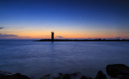 Sunrise over lighthouse with moon on the sky. Stock Photo
