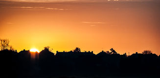 Sunrise over line of houses. Line of private residences or houses with the first glimpse of the rising sun Stock Photo