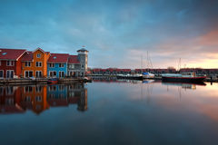 Sunrise over marina with buildings and boats Stock Image
