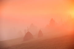 Sunrise over mountain field. Haystacks in misty autumn morning h Royalty Free Stock Images