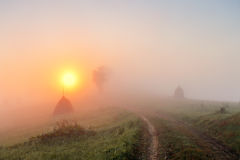 Sunrise over mountain field. Haystacks and road  in misty autumn Royalty Free Stock Images