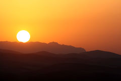 Sunrise over the mountains. A picture of the sun rising over the silhouette of the mountains. The sky has been painted orange by the sun's rays stock image