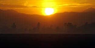 Sunrise over mountains of Java Indonesia. Bright golden sunrise over volcanic mountains of the island of Java, Indonesia. Tropical rainforest Stock Image
