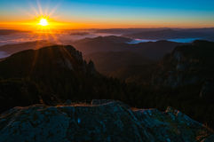 Sunrise over the mountains. Misty morning with sun over the mountains in National Park Ceahlau Stock Photos