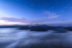 Sunrise over Mt. Bromo, Indonesia. Blue and purple skies with stars over Mt. Bromo with mist at sunrise, Indonesia stock photos