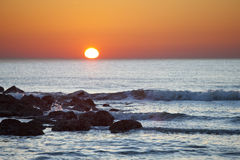 Sunrise over the ocean. With foreground rocks Stock Image