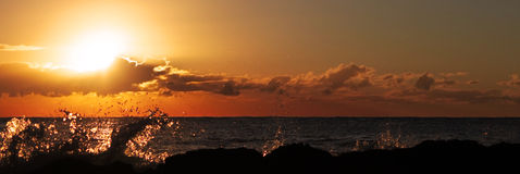 Sunrise over the ocean. Sun rising over the waves of the coastline Royalty Free Stock Image