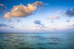 Sunrise over the ocean. Sunrise over the turqoise ocean with blue sky and some clouds Royalty Free Stock Photography