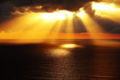 Golden sunlight through dark clouds over ocean. Aerial image showing a sunrise over the dark ocean with sun rays streaming through low altitude storm clouds - at Royalty Free Stock Photos