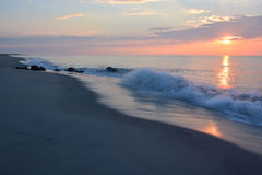 Sunrise Over Ocean with Breaking Waves. The sunrises over the ocean on a summer morning Royalty Free Stock Photography