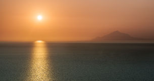 Sunrise over the ocean with burnt orange sky Royalty Free Stock Images