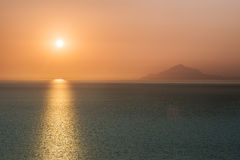 Sunrise over the ocean with burnt orange sky Stock Photography