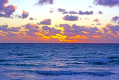 Sunrise over the ocean with clouds. Magenta morning over the ocean Stock Photography