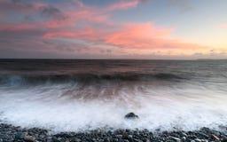 Sunrise over the ocean. Sunrise at Clovelly beach in Devon Stock Photo