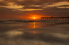Sunrise. Over ocean in daytona beach florida  with pier and beach in foreground Royalty Free Stock Photography