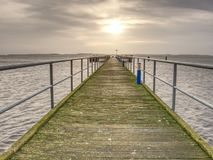 Sunrise over ocean. The empty wooden pier at moody colorful morning. Tourist wharf in bay at smooth sea stock photography