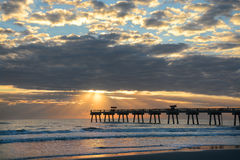Sunrise over ocean horizon and pier. Stock Images