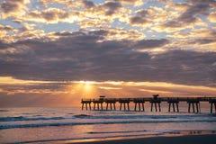 Sunrise over ocean horizon and pier. Stock Photos