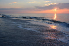 Sunrise Over Ocean and Jetty. The sunrises over the ocean on a summer morning Stock Photo