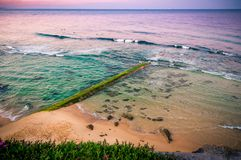 Sunrise over the ocean. Old stone pier overgrown with algae. Australia, NSW, Newcastle. stock images