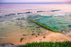 Sunrise over the ocean. Old stone pier overgrown with algae. Australia, NSW, Newcastle. royalty free stock photos