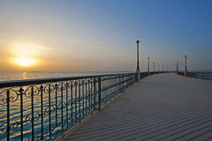 Sunrise over the ocean at a pier Royalty Free Stock Image